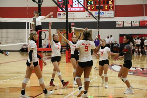 The varsity volleyball team celebrates after scoring. The team won this match.