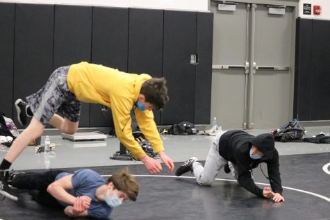 The wrestling team sharpens their moves while still trying to fight against COVID-19 by wearing their masks during practice. Many practices start with warming up and basic drills in their team pods to reduce risk of infection amongst the group as a whole.