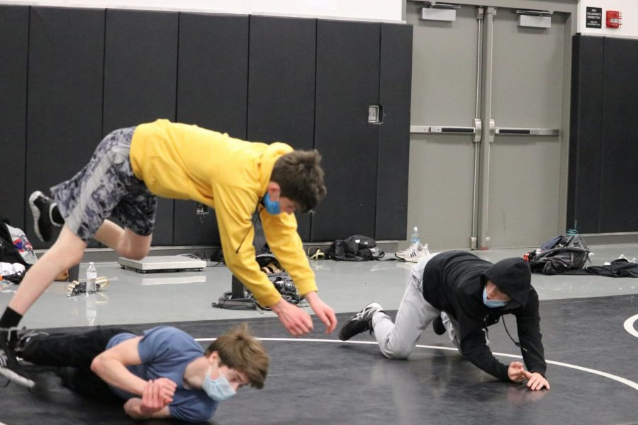 The wrestling team sharpens their moves while still trying to fight against COVID-19 by wearing their masks during practice. Many practices start with warming up and basic drills in their team