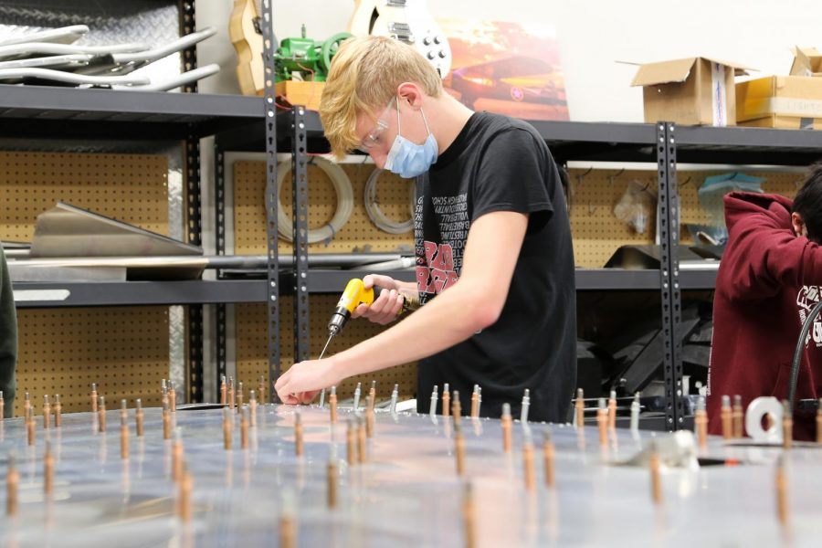 Junior Liam McDaniel installs rivets into a wing of the MCA aircraft. Students from Maize and Maize South work together every year to build an airplane that will later be flown after completion.