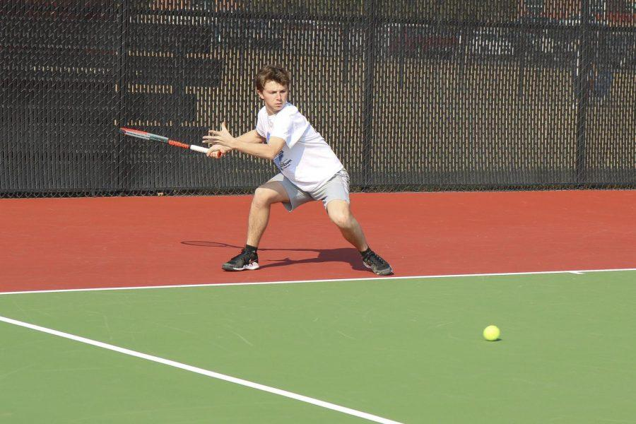 Harris Kossover (11), sets his feet up to execute a forehand shot against his opponent. In order to keep his form correct, Kossover sets his feet apart and bends his knees to hit the low-landing ball back to his team.
