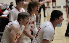 The basketball team cheers on their teammates on the sidelines.