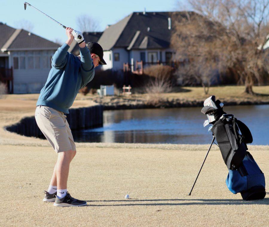 Bringing his club back to strike the ball, junior Taben Armstrong delivers a swing on his second shot on hole 3 around the edge of a pond at Auburn Hills on Tuesday, Mar. 2.