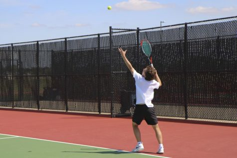Junior Harris Kossover prepares to serve the ball against his opponent school, Campus. Kossover lost only one game in the match while winning 11, pushing Maize South even closer to their first place win.