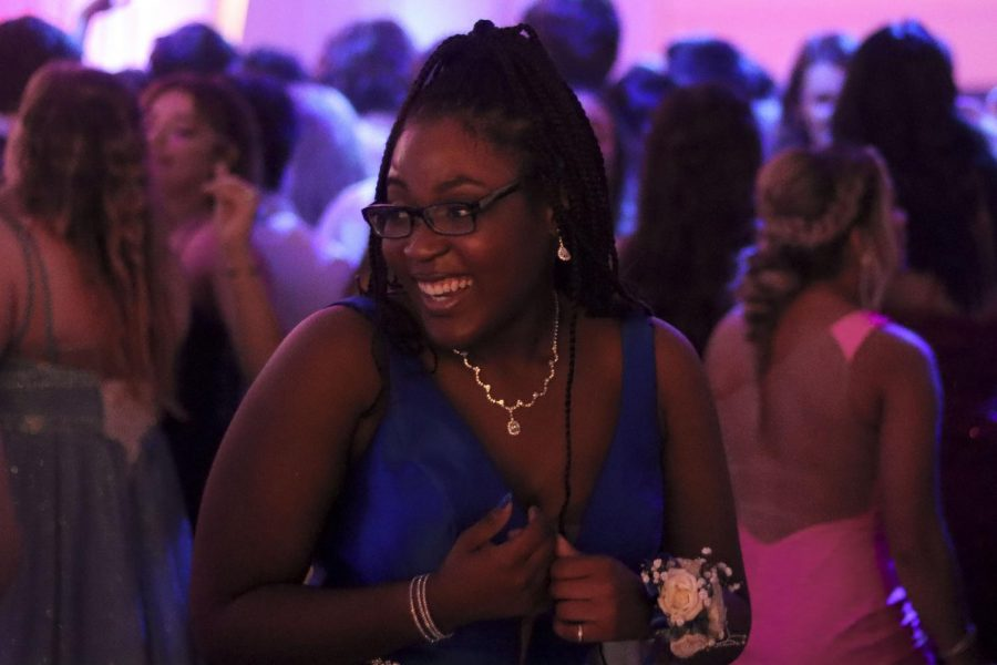 Senior Kiara Colbert laughs as she talks to her friends and enjoys her time at prom. Colbert wore a dark blue dress with her hair in a high ponytail and matching heels and jewelry.