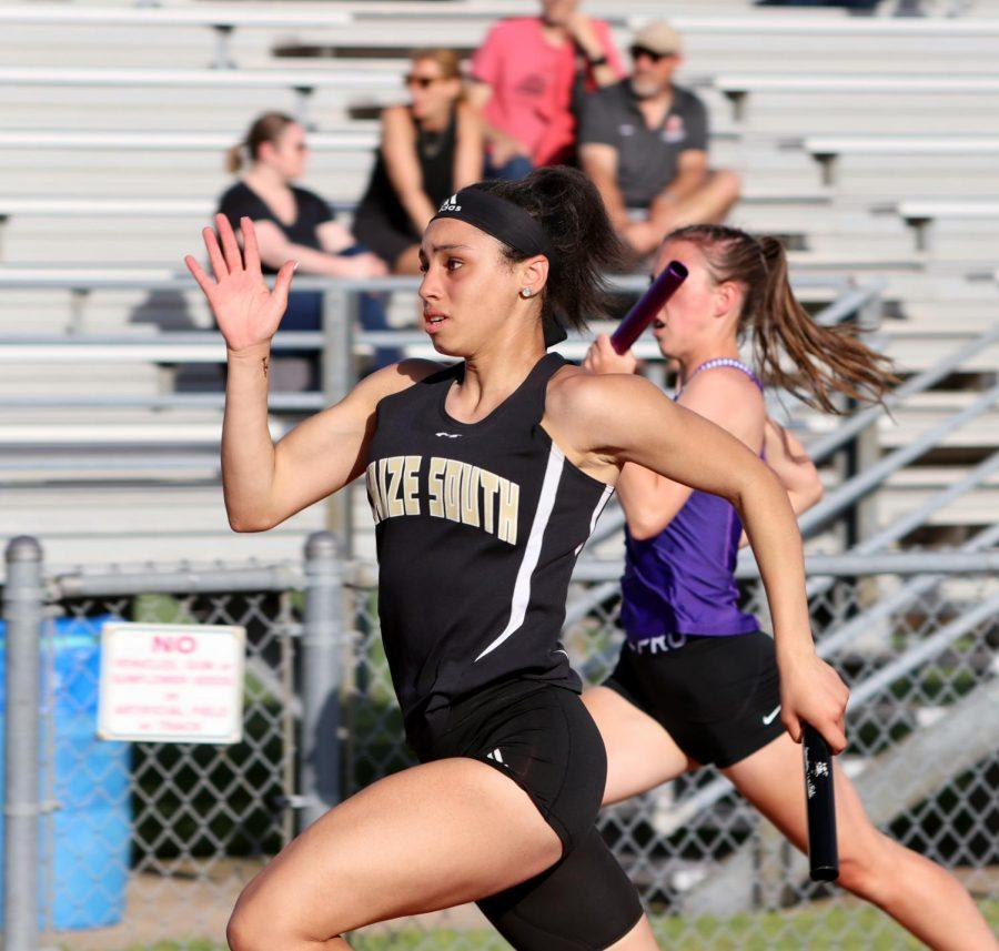 During the 4x100 Relay, Lily Mitchell (10) keeps up with the other schools to stay in front to pass the baton on Friday, May 21. Over a dozen lady runners placed at regional event.