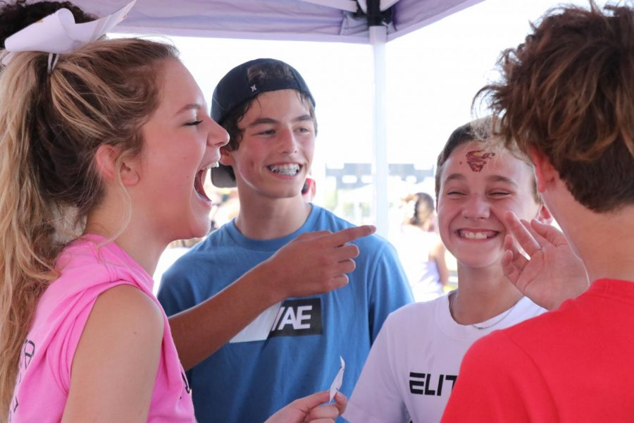 Having a good and wild time, eighth-graders Reece Pauly and Cooper Riley are participating in getting a tattoo from Senior Axie Sanchez at the Maize South cheer teams booth.