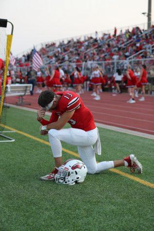 Senior Landon Helm prays on the sideline just shortly before kickoff.