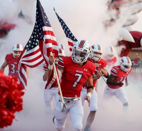 Junior Cooper Burke rushes the field carrying a flag. Thirteen players carried flags to commemorate the soldiers who lost their lives in Afghanistan.
